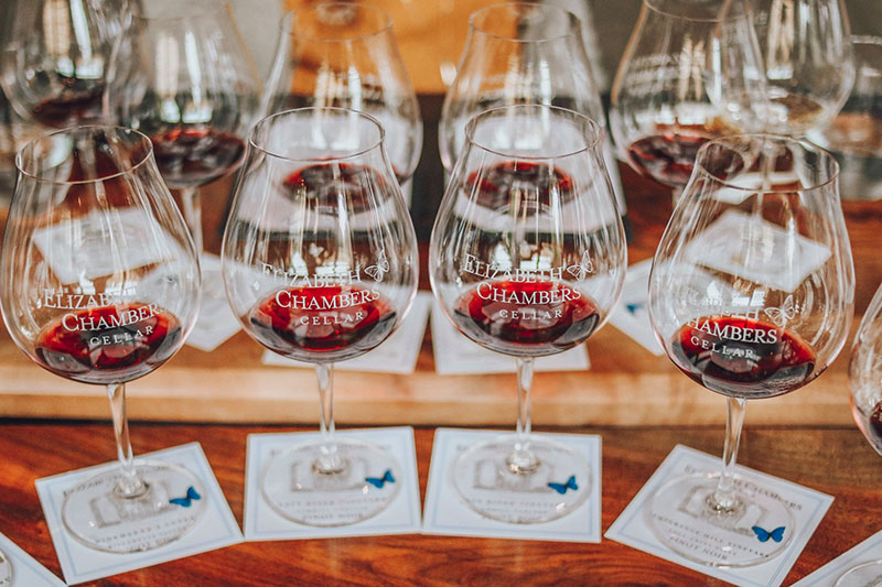Elizabeth Chambers Cellar logo glasses with wine